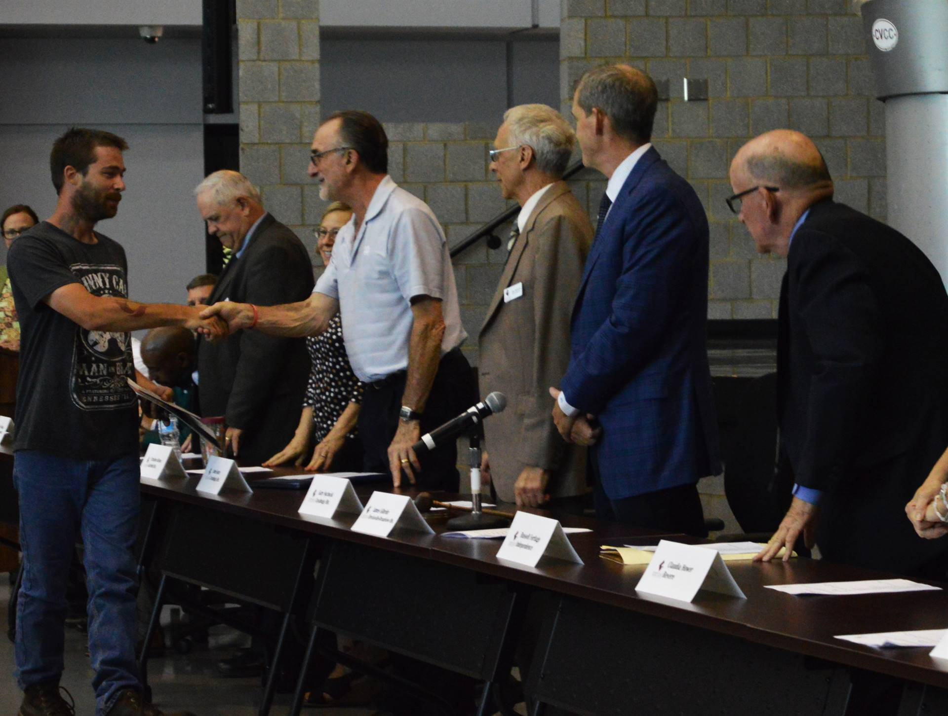 Adult student shaking hands with Board members