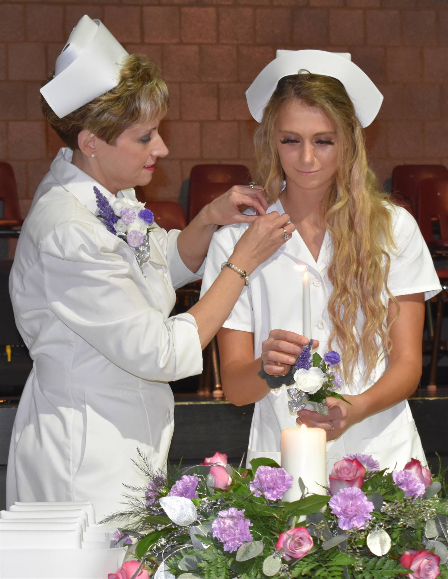 student receiving pin and lighting candle